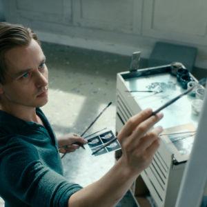 Kurt Barnert (Tom Schilling) maalaa ateljeessaan. Kädessä hänellä on mallina neljän passikuvan arkki.