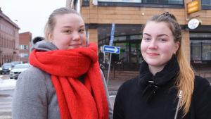Två unga vinterklädda kvinnor står i centrum av Borgå. De tittar båda in i kameran.