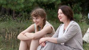Malin (Saga Sarkola) och Salome (Satu Tuuli Karhu) sitter bredvid varandra på en strand och ler.