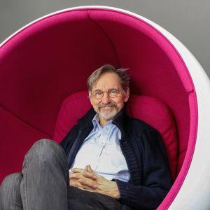 Asko Sarkola sitter i en vit-pink stol designad av Eero Aarnio.