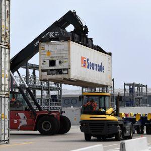 Kuormaaja nostaa konttia kuljetusajoneuvon kyytiin satamassa.