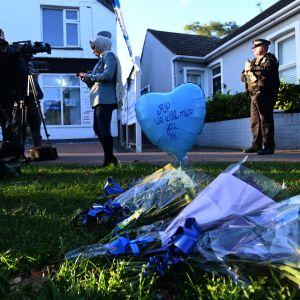 Blombuketter ligger på gräset framför det hus där den brittiska parlamentariken David Amess bodde.