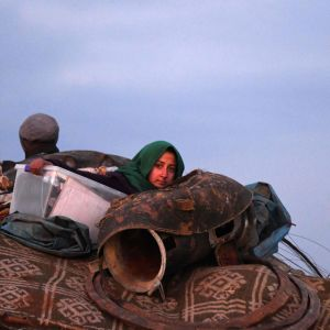 En flykting omgiven av möbler och mattor sitter på flaket på en lastbil norr om Aleppo.