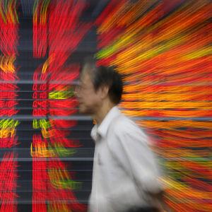 Thailändsk investerare passerar en elektronisk tavla som visar fallande börskurser 07012016
