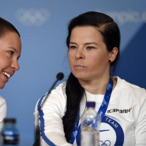 Kerttu Niskanen viskar något åt Krista Pärmäkoski på en presskonferens.