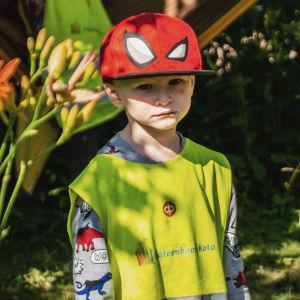 Pojke i röd skärmmössa och neongul reflexväst och allvarsam blick står i en grönskande trädgård.