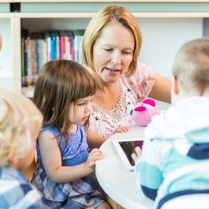 En vuxen kvinna sitter vid en pekplatta tillsammans med några barn.