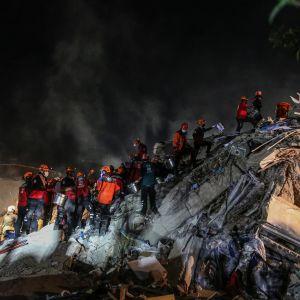 Räddningsmanskap i röda hjälmar och jackor klättrar på ett berg av rasmassor. Det är mörkt.