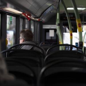 Matkustajia linja-autossa Helsingissä.