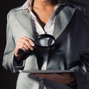 En affärskvinna står med ett papper i handen och håller upp ett förstoringsglas.