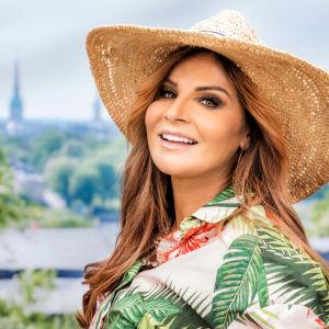 Carola Med en sommarhatt och blommig skjorta.
