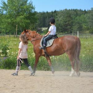 En tolvårig flicka leder en häst som en mindre flicka rider på, på en sandplan.
