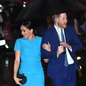 Meghan ja Harry hymyilevät sateenvarjon alla