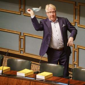 Veikko Vallin, en äldre man, snurrar ett munskydd ovnför huvudet i riksdagen