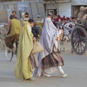 Kaksi naista Afganistanissa kävelee kantaen lasta sylissään..