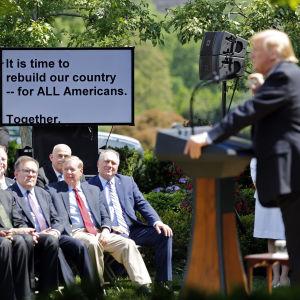 Trump i talarstolen framför rad av män i svart kostym, bakom dem presidentens teleprompter