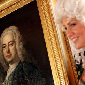 Dam i peruk visar upp en tavla som föreställer Georg Friedrich Händel