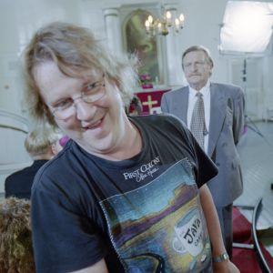 Ohjaaja Jukka Mäkinen työssään Mooseksen perintö -sarjan kuvauksissa vuonna 2001. Taustalla näyttelijä Matti Tuominen (roolinimi Urmas Hakkarainen).