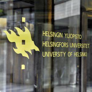 """Bild på glasdörr vid Helsingfors universitet. På dörren står universitetets logotyp och och texten """"Helsingfors universitet""""."""