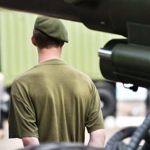En beväring i grön barett står med ryggen vänd mot kameran händerna knäppta bakom ryggen.