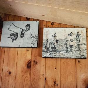 Två svartvita fotografier på en trävägg. Bilderna föreställer inuiter på Grönland.
