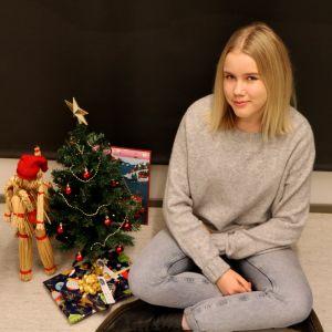 Anna sitter på golvet intill en julgran och annat julpynt.
