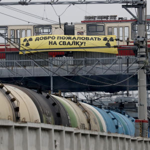"""En spårvagn och en gul banner med texten """"välkommen till skräpdumpen"""" på ryska."""