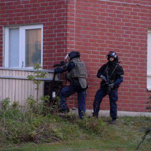 Poliser utanför ett rött tegelhus. De har tunga vapen och skyddsvästar på sig.