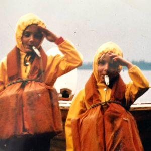 Mari Rosendahl sisarensa kanssa pikkutyttöinä poseeraamassa käsi lipassa veneen vieressä yllään sadetakit ja pelastusliivit.