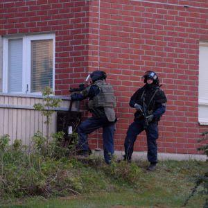 Polis i tung utrustning utanför en lägenhet i Mäkkylä, Esbo.