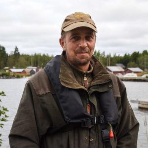 Man i jaktkläder och flytväst tittar in i kameran, i bakgrunden syns en småbåtshamn.