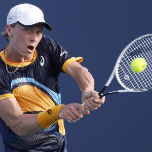 Emil Ruusuvuori i mörkblå blus slår till bollen med sin racket.