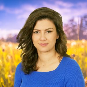 Rebecka Sretenovic småler in i kameran med en sommaräng i bakgrunden.i bakgrunden.
