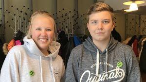 Matilda och Wille i grå tröjor framför garderoben på kulturhuset grand.