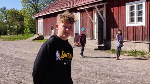 En ung pojke står på en skolgård.