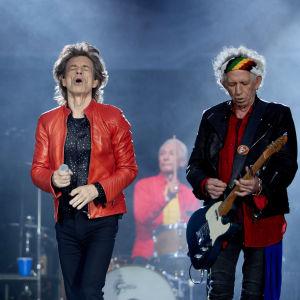 På bilden syns bandet Rolling Stones uppträda under en konsert i Berlin år 2018. I mitten står sångaren Mick Jagger klädd i en röd läderjacka.