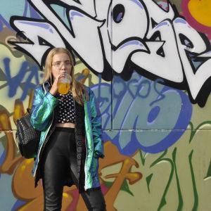 Milla står med ett glas med en orange dryck i sin högra han framför en grafittivägg. Hon tittar in i kameran, och har en ryggsäck med nitar på sin högra axel.