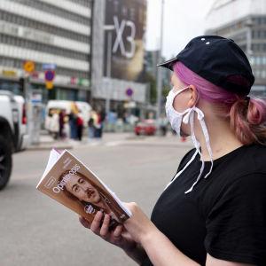 Nuori nainen lukee opinto-opasta kasvomaski naamallaan Helsingin keskustassa.