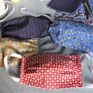 Munskydd av tyg i olika färger och mönster ligger på ett bord.