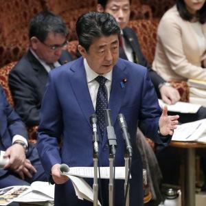 Japans premiärminister Shinzo Abe står i ett talarpodie i Japans parlamet och håller tal om bland annat att sommar-OS i Tokyo kan komma att flyttas p.g.a coronapandemin. I bakgrunden sitter fyra personer, varav en bär ansiktsmask.
