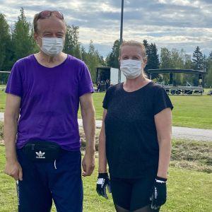 En man och en kvinna med munskydd står framför en gräsplan och tittar in i kameran. Bakom dem syns en scen som håller på att byggas upp.