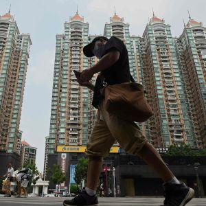 Jalakulkija ohittaa isot tornitalot.