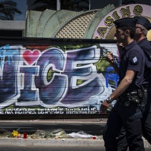 Två poliser går förbi en graffitimålning som hedrar offren i attacken i Nice.