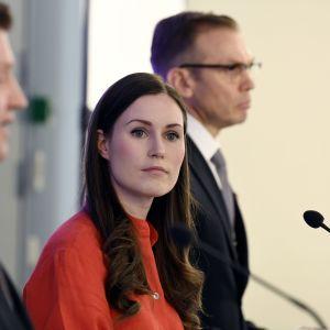 Bild från en presskonferens. Två män på vardera sida om statsminister Sanna Marin. Kameran fokuserar på Marin som ser ut att lyssna på någon utanför bild.