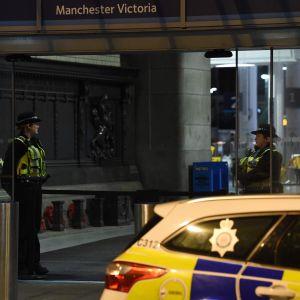 Poliser och en polisbil utanför tågstationen Manchester Victoria efter knivattacken på nyårsafton.
