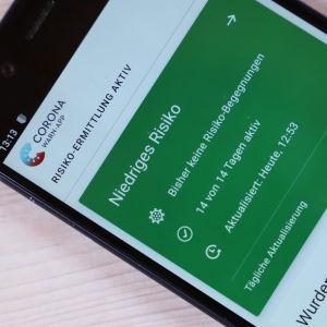 Mobiltelefon med den tyska corona-appen på skärmen