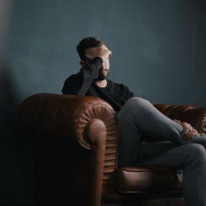 Mies istuu nojatuolissa ja peittää kasvonsa kädellä.