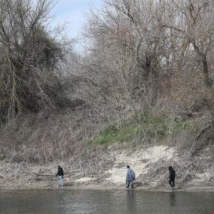 Kolme miestä kulkee Evros-joen vartta maaliskuussa 2020.