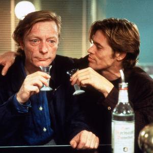 Cassiel (Otto Sander) ja Emit Flesti (Willem Dafoe) juovat viinaa elokuvassa Niin kaukana, niin lähellä