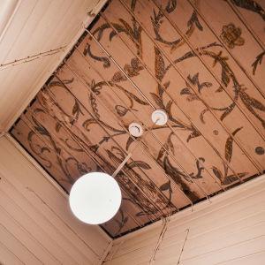 Kuva kirkon sisäkatosta, ruskeita lehtikuvioita, valkoinen lamppu